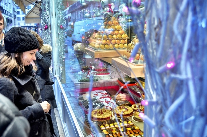 6. Visitors admire the elaborate holiday pastries and desserts shops display in their windows